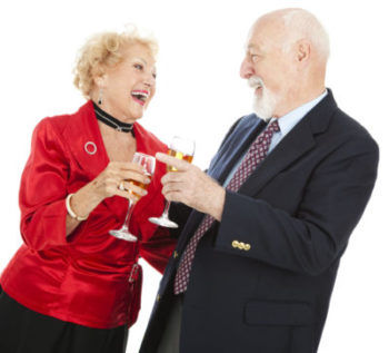Senior couple celebrating a holiday with champagne. Isolated on white.
